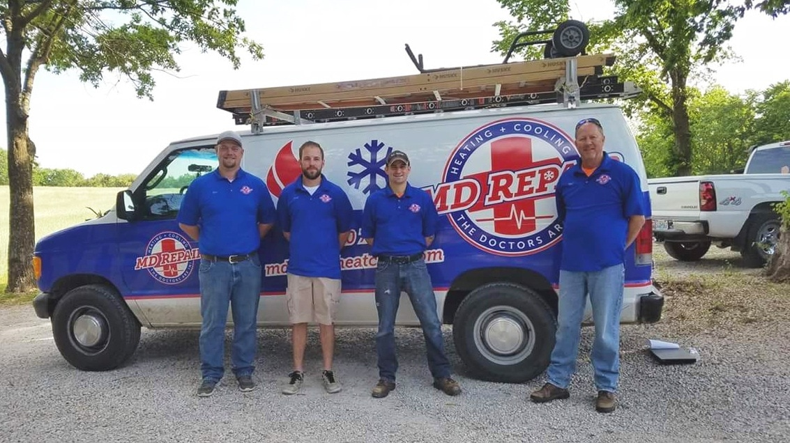 MDR Repair workers standing in front of a company van.